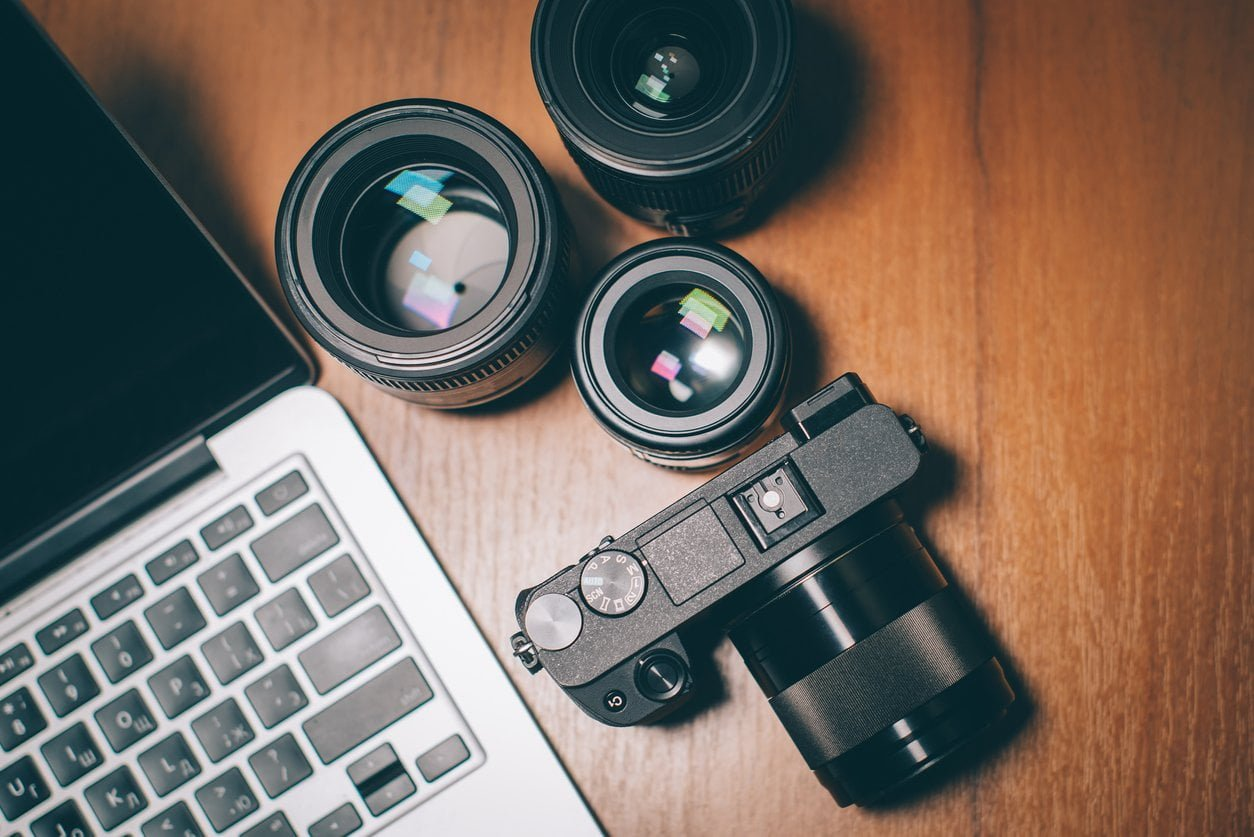 top view of the photographer's workplace, camera, lenses and computer